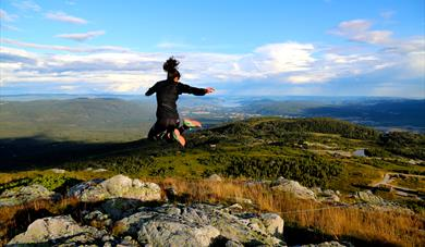 Photo from one of Lifjell's many summits. Blue sky, beautiful view of lake Norsjø and Telemark, and a girl jumping high in the air.